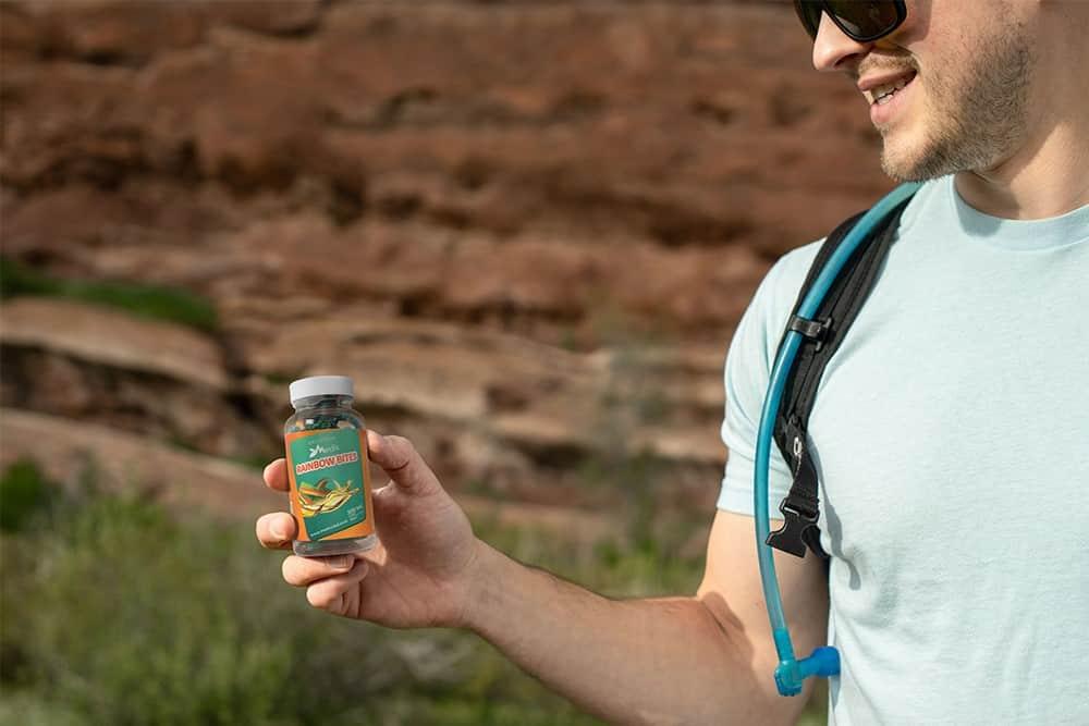A man holds a bottle of CBD gummies outdoors
