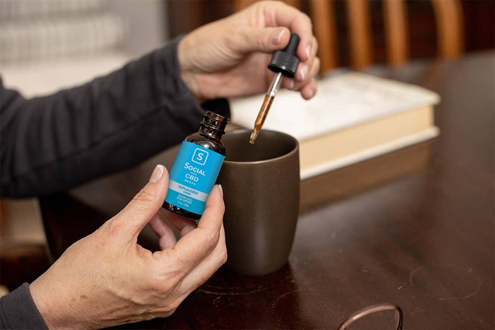 A user drops her dose of Social CBD tincture into a coffee mug while seated at a dark wood table