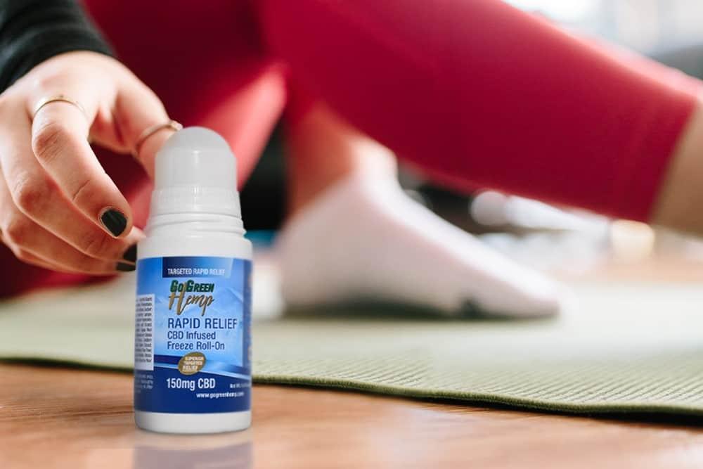 A neck pain sufferer reaches for a bottle of GoGreen Hemp Freeze Roll-On