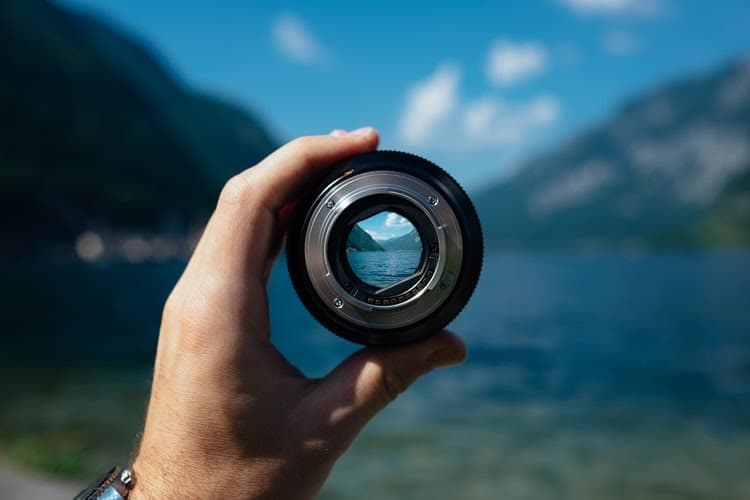 Someone holds up a camera lens focused on a blue lake, while the lake, mountains, and sky in the rest of the picture is blurry and out of focus