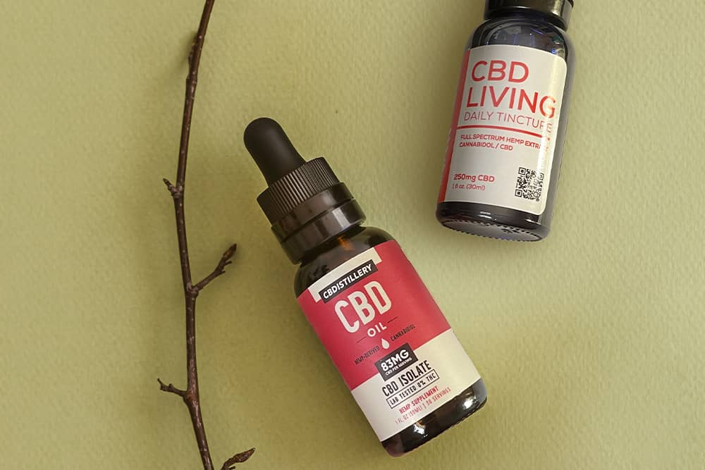 Some CBD products laid out on a table with a vine or something.