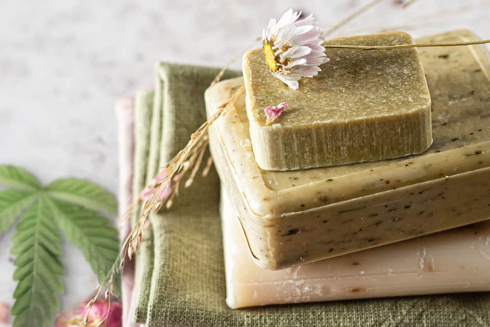 Some bars of CBD soap stacked on top of one another. There's also a hemp leaf to the side and some random sage or lavender thrown around for some reason.