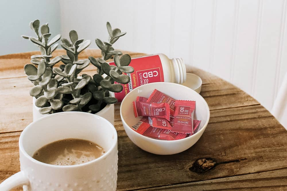 A bowl of delicious CBD lozenges beside a cup of coffee; we do not recommend this flavor combination, but you do you.