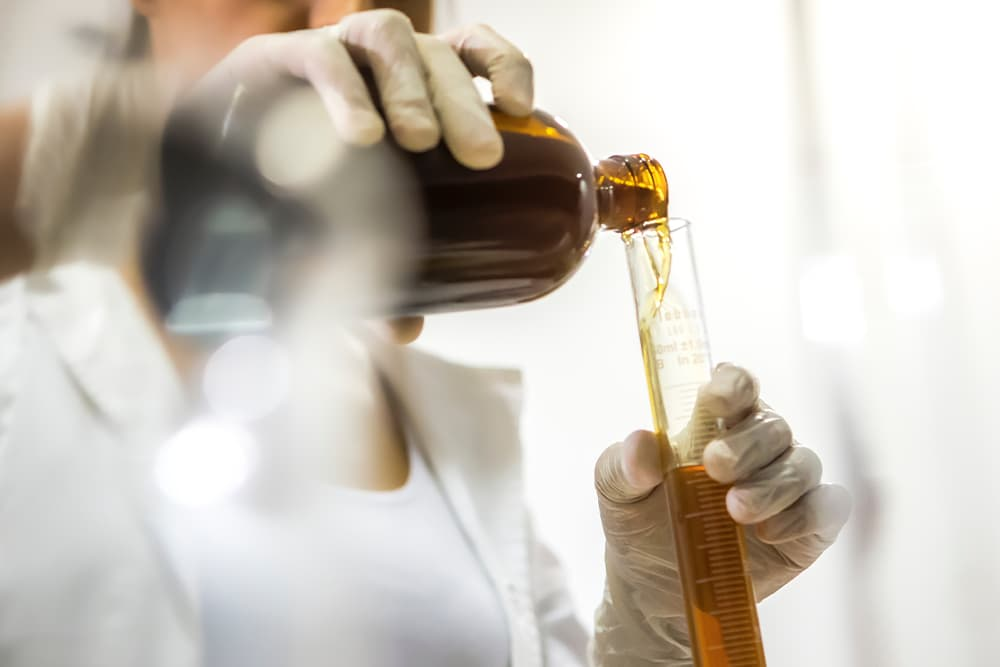 Scientist pours CBD oil to test for antimicrobial effects