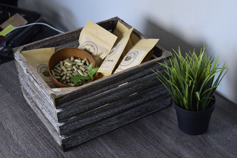 Wooden box with Kratom packets and capsules