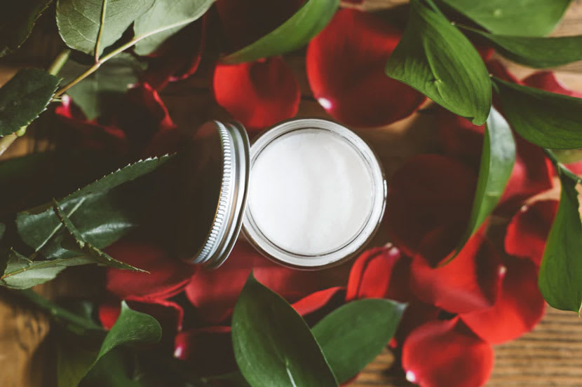 A jar of face cream surrounded by leaves