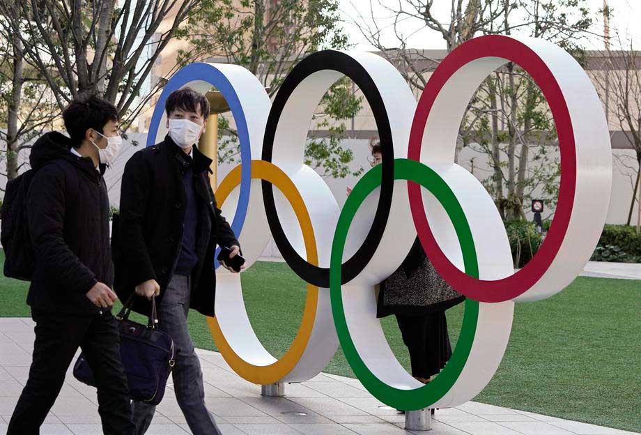 Japoneses usando máscaras caminham em frente ao símbolo dos Jogos Olímpicos em Tóquio