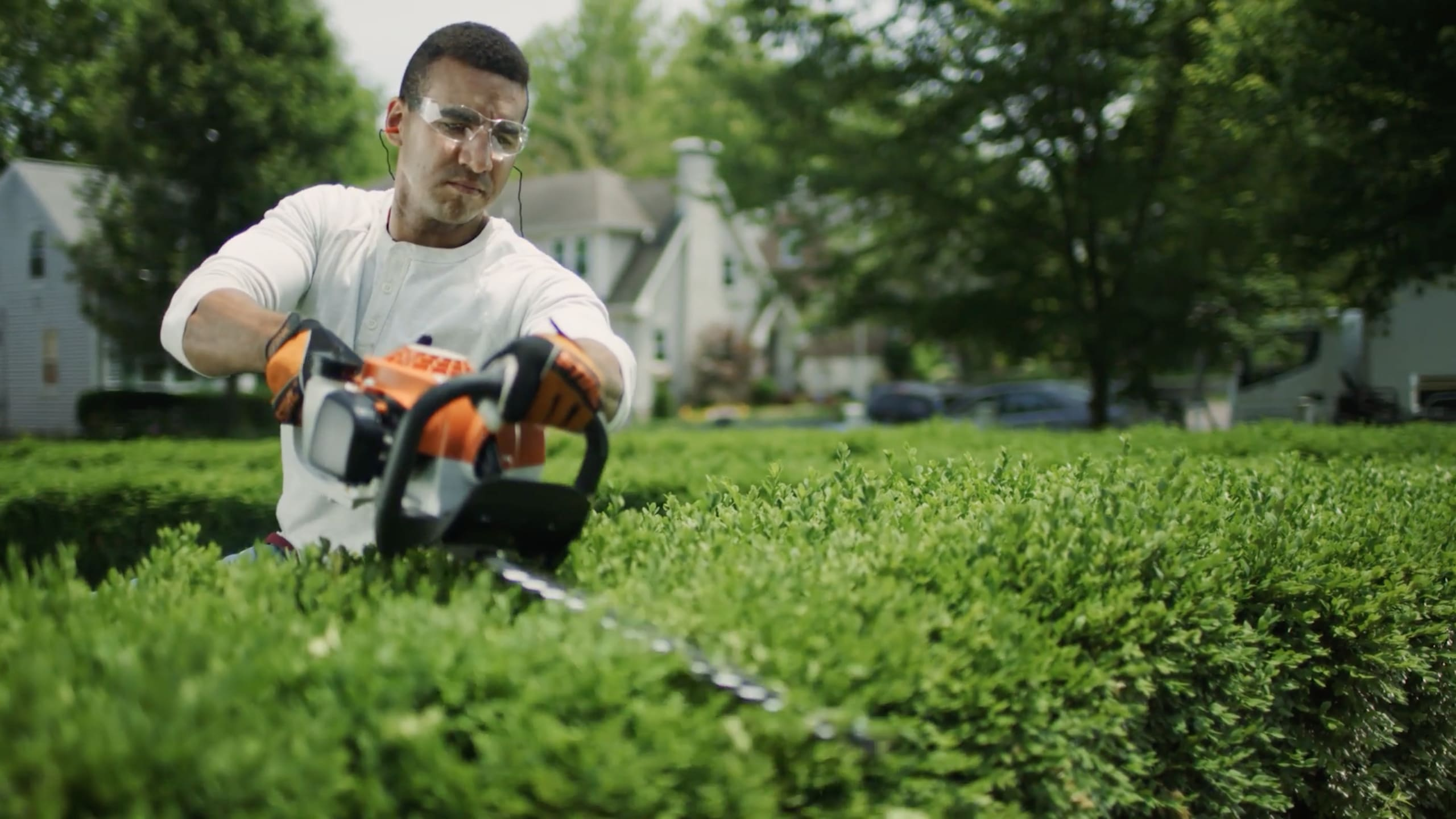 A man trimming his bushes with a stihl chainsaw