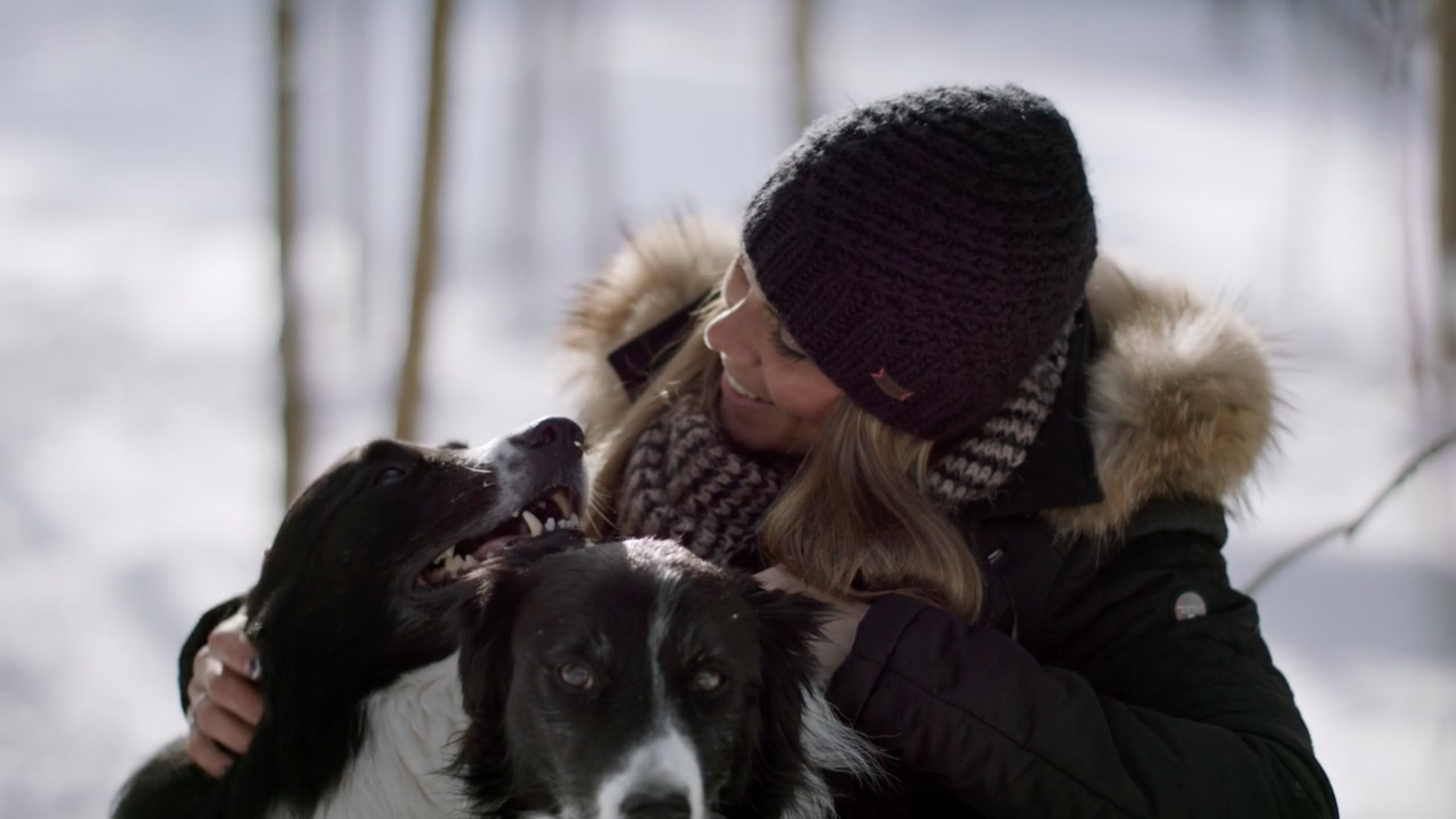Amber playing with her two dogs in the snow