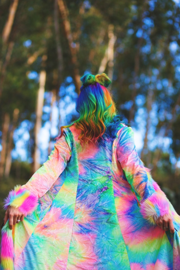 Rainbow haired girl wearing an all rainbow tie dye look, including our shag jacket and bubble yoga bells.