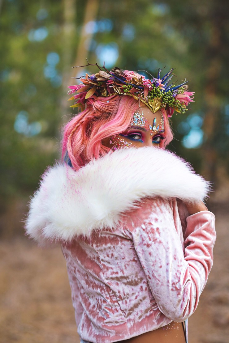 Pink hair glitter girl stares over her right shoulder wearing our faux fur fluffy goddess jacket.