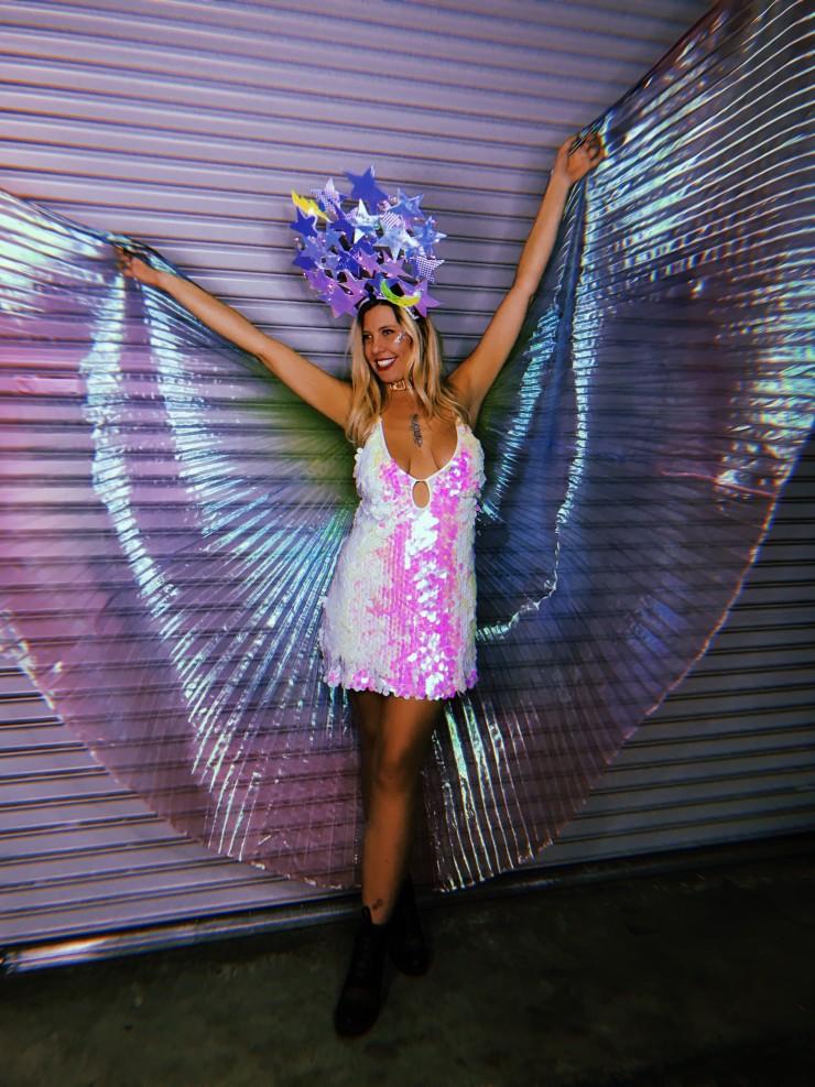 A rainbow rave babe wearing our shakedown fringe jacket and alien leggings poses sweetly.