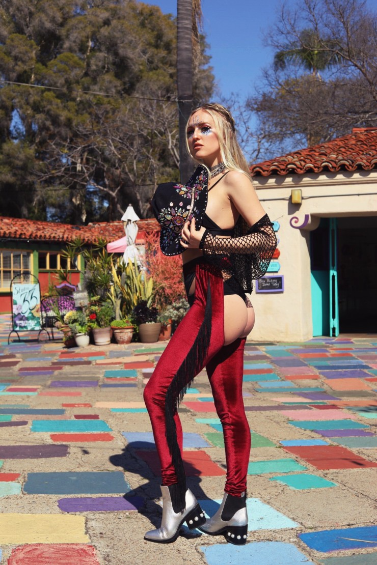 A blonde bejeweled cowgirl wearing red velvet chaps steps forward in a rainbow brick Spanish Village Art center in Balboa Park.