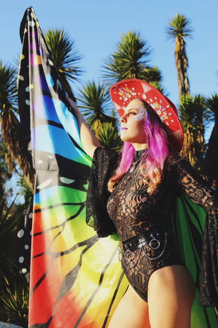 A sunset haired rhinestone cowgirl with a red bejeweled hat looks off into the sunset wearing a lace black bodysuit with bell sleeves and rainbow butterfly wings.
