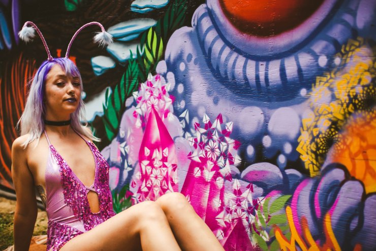 Our purple haired moth girl sits in front of hot pink and white spray painted sacred geometry mural art.