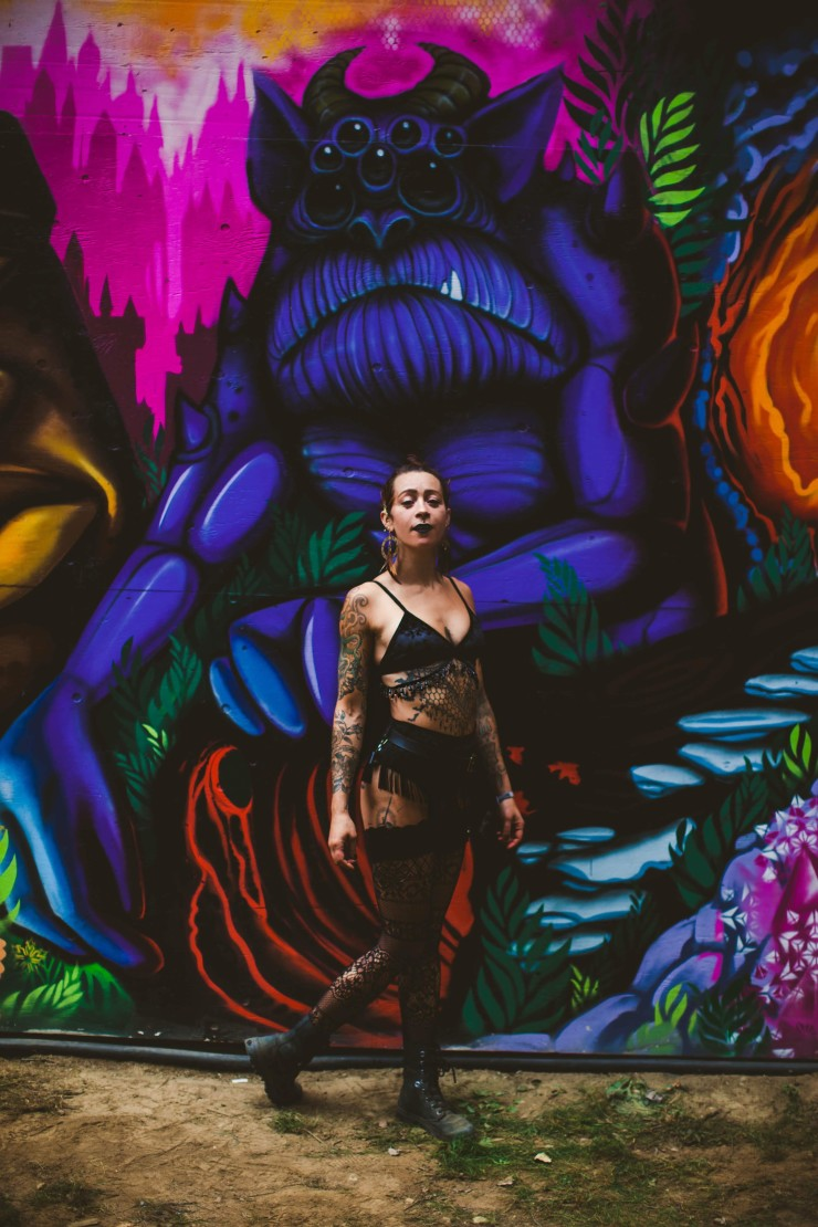 A girl wearing a black velvet beaded and fringe two piece set stands in front of a colorful mural featuring a horned monster with an under bite and seven eyes.