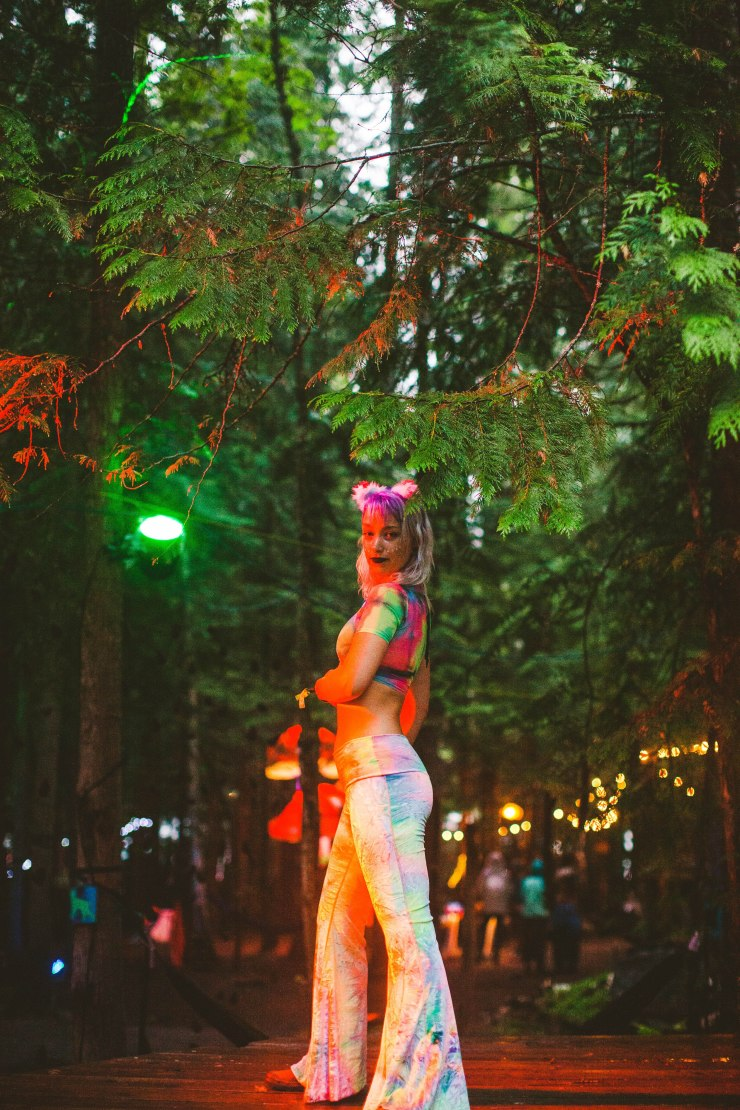 A cat ear wearing girl in a rainbow tie dye mesh crop tee and matching bell bottoms stands in the forest bathed in warm neon orange light.
