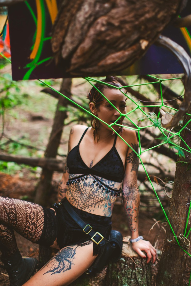 Our black velvet tattooed beauty sits on a tree stump behind a green rope spider web.