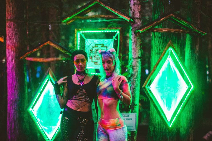 Two girls wearing black and rainbow clothing stand in front of light up green diamond art at Shambhala.