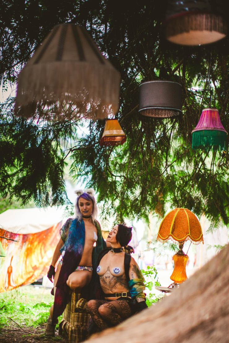 Two girls in cat ears and pasties sit in a garden of vintage lamp shades under a tree at Shambhala.