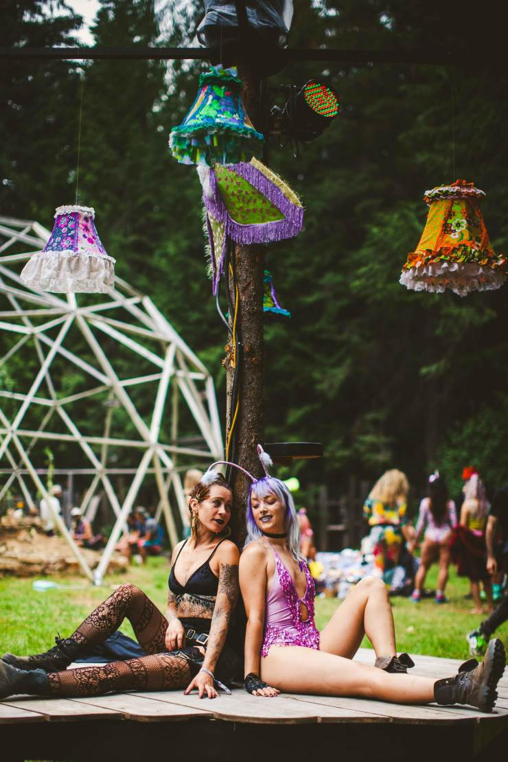 Two girls at Shambhala music festival sit back to back on an art installation platform, leaning on a wooden pole with hanging vintage lamp shades at the top.