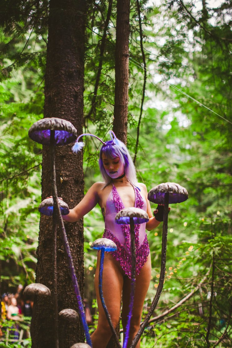A lavender haired girl wearing a fuzzy moth antennae headband and a purple sequin bodysuit stands among a light up mushroom sculpture.