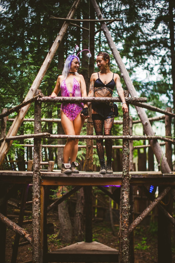 Two girls, one wearing a purple sequin bodysuit and one wearing a black velvet beaded and fringe two piece outfit, stand in a triangular tree house smiling at each other.