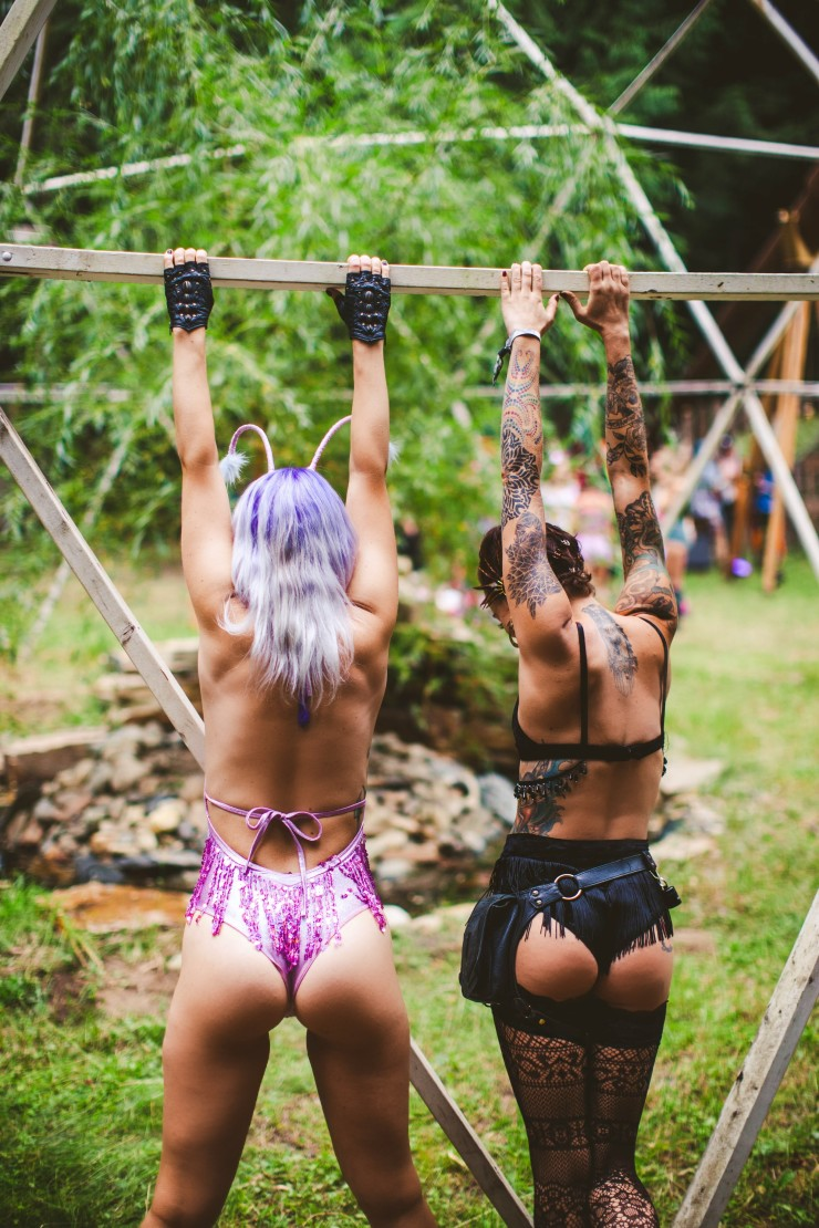 Two girls, one wearing a purple sequin bodysuit and one wearing a black velvet beaded and fringe two piece outfit, reach up with their hands and hang from a metal bar, showing off their nice booties.