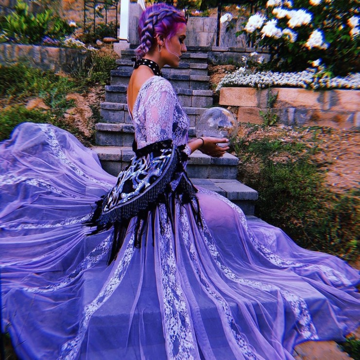 A girl with purple braids kneels on stone steps with a glass globe in her hands, wearing a long lavender gown and a matching sequin shawl.