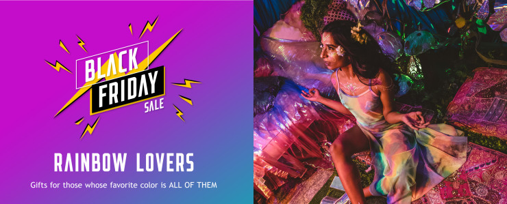 Rainbow lovers gift guide. Brunette girl wearing a rainbow mesh sleeveless maxi dress with flowers and glitter sitting in darkly lit colorful room.