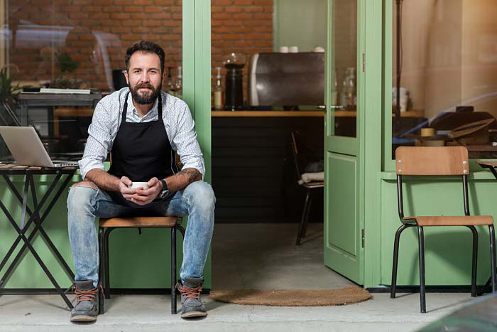 Content café owner sits in front of his store with laptop