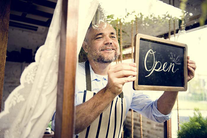 Smiling business owner places open sign in window