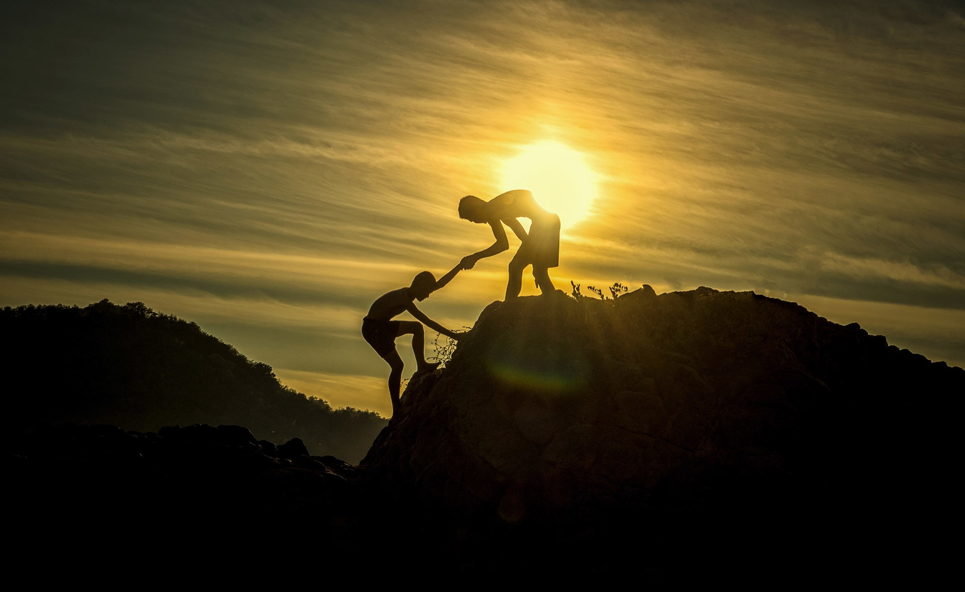 Person helping someone up a mountain
