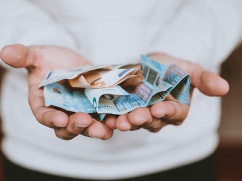 zwei Handflächen, die zu einer Schale geformt sind und Geldscheine beinhalten