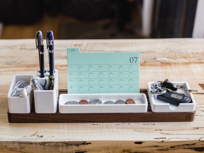sehr aufgeräumter Schreibtisch mit einzelnen Boxen für Stifte, Kopfhörer, Autoschlüssel, Münzen und Terminplaner