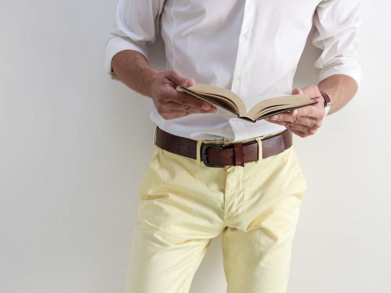 Mann im weißen Hemd und gelber Hose hält aufgeschlagenes Buch in den Händen
