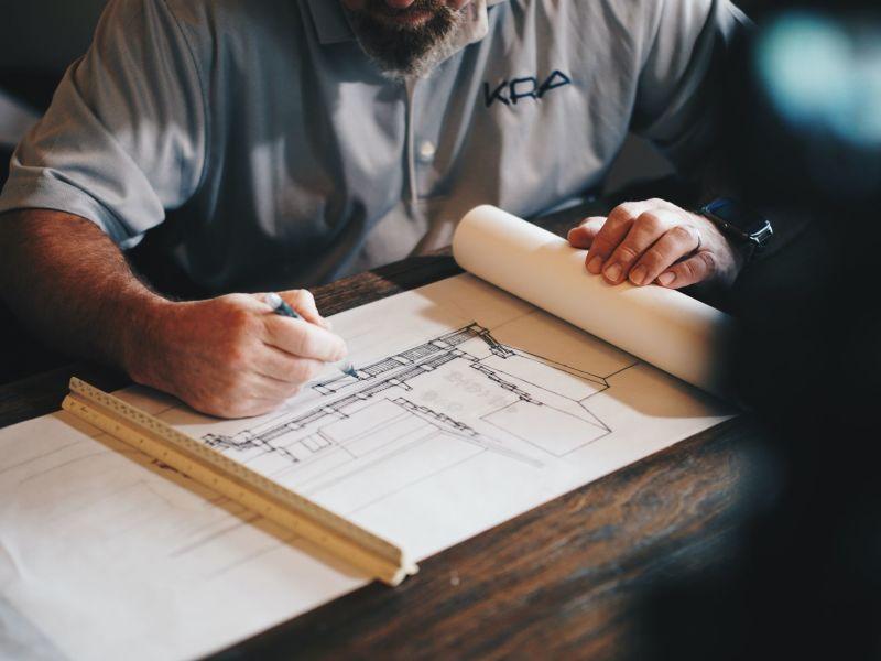 Ein älterer Mann mit Bart sitzt an einem Tisch über eine Zeichenrolle gebeugt und skizziert einen architektonischen Entwurf.