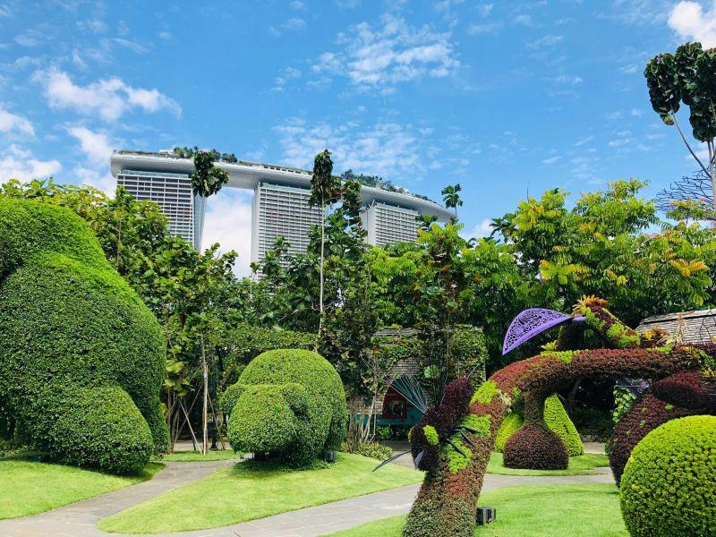 Ein Park in Singapur mit zu Tieren geformten Büschen und Skulpturen. Im Hintergrund sind 3 Hochhäuser zu sehen.