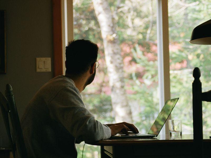 Mann sitzt an einem Esstisch vor seinem Laptop und schaut durch ein großes Fenster in einen Wald.