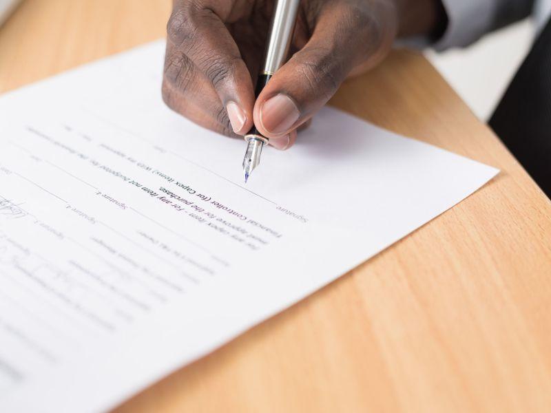 Hand mit Füller unterschreibt ein Dokument