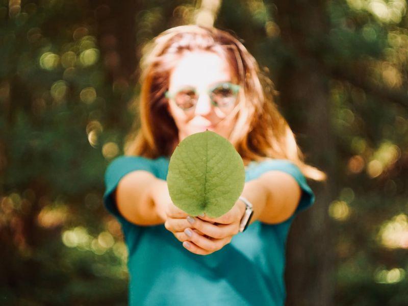 Frau mit Brille hält ein grünes Blatt mit beiden Händen direkt in die Kamera