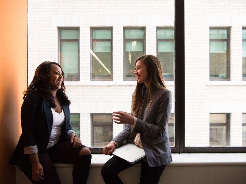 Zwei junge Frauen sitzen lachend auf einer Fensterbank