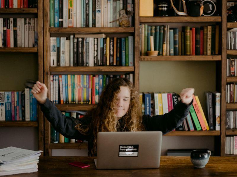 Mädchen sitzt in Sieges-Pose vor einem Bücherregal an einem Schreibtisch vor dem Laptop