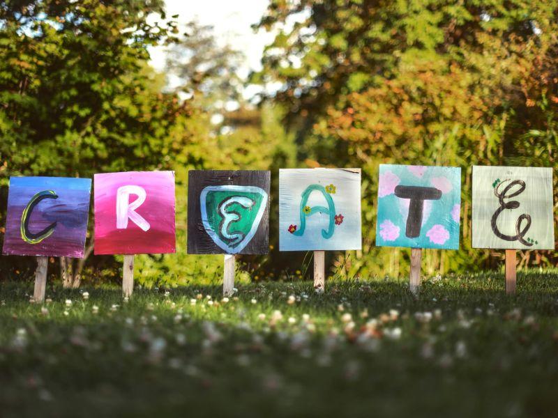 """Auf einer grünen Wiese stehen 6 Schilder mit Buchstaben, die insgesamt das Wort """"create"""" ergeben."""