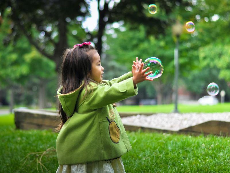 Mädchen läuft staunend einer Seifenblase hinterher
