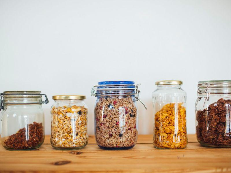 Fünf Einweggläser nebeneinander, gefüllt mit verschiedenen Cerealien