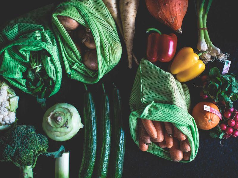 verschiedene, bunte Gemüsesorten, manche davon in grünen Gemüsenetzen