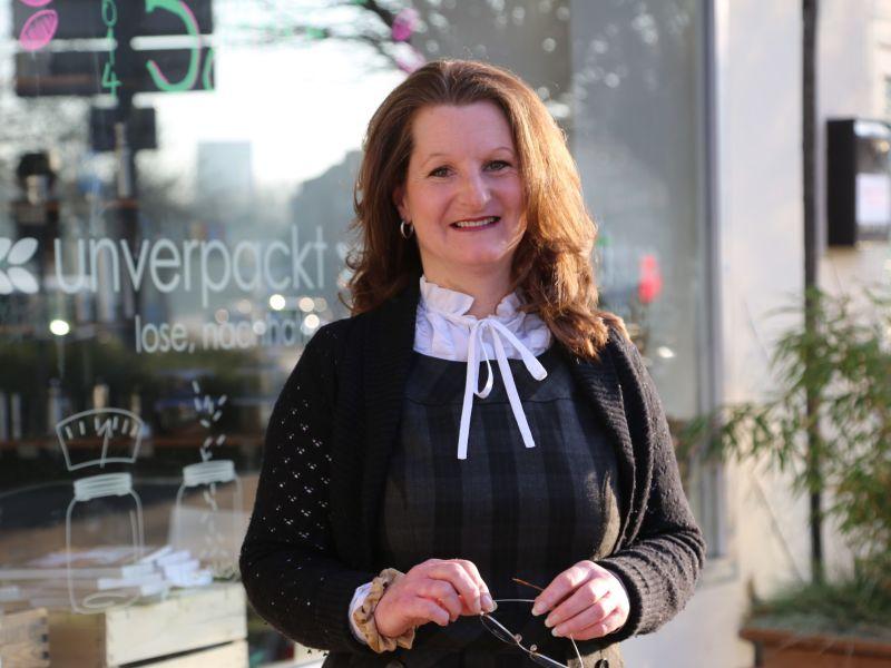 Marie Delaperrière, die Gründerin von Unverpackt Kiel steht vor dem Schaufenster ihres Ladens