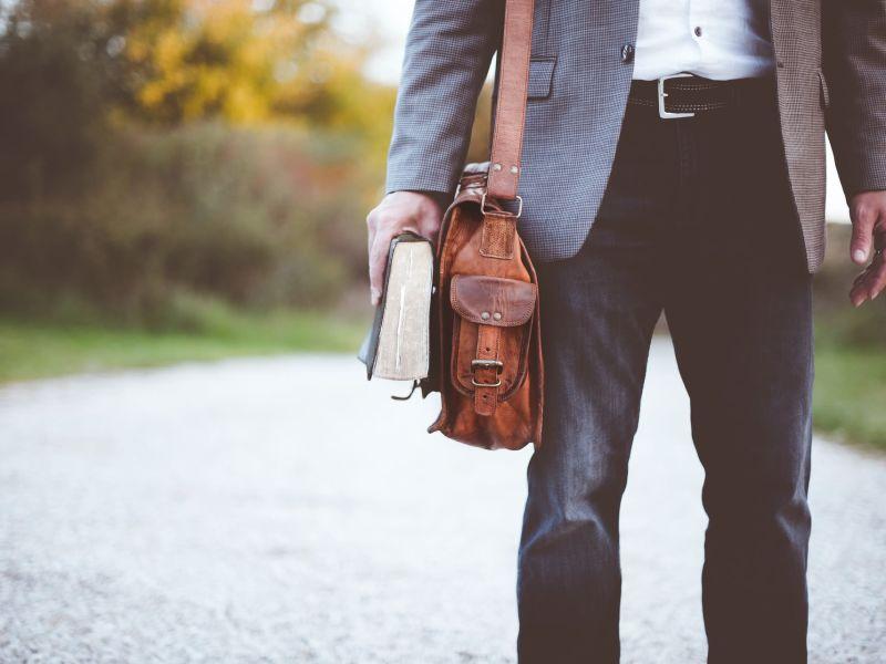 Mann mit Ledertasche und Buch in der Hand