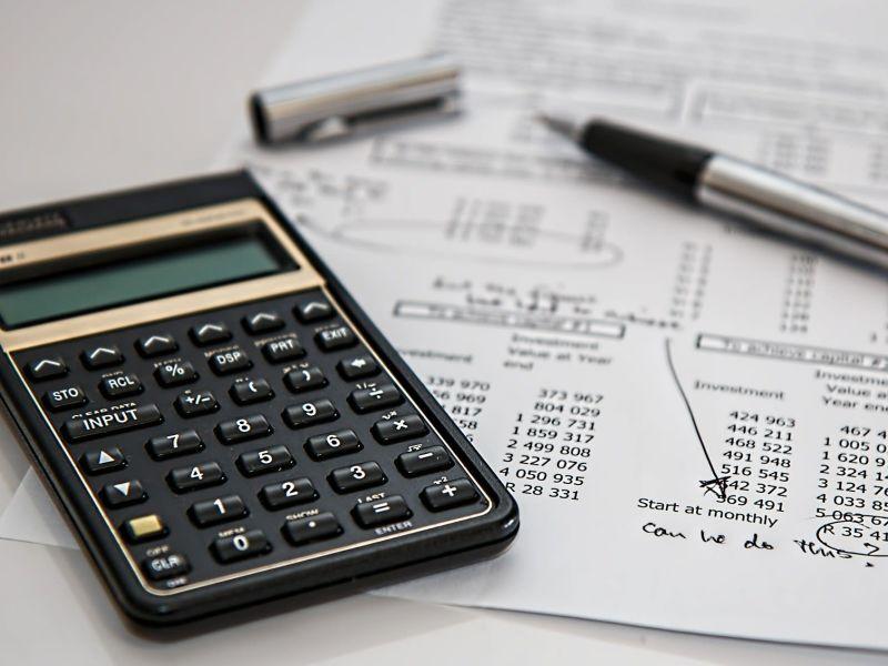 Taschenrechner, daneben ein Zettel mit Kalkulationen und einem Stift